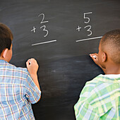 Boys solving math problems on blackboard, Jersey City, New Jersey, USA