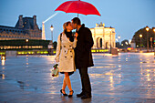 Caucasian couple kissing in rain at night near the Louvre, Paris, Paris, France