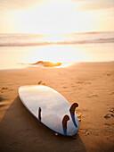 Surfboard laying on beach at sunset, Dana Point, CA, USA