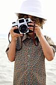 Mixed race boy using old-fashioned camera, San Diego, CA, USA