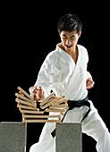 Asian male karate black belt breaking wooden planks, Jersey City, NJ, USA