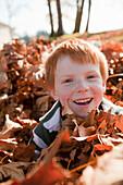 Caucasian boy playing in autumn leaves, Nanaimo, British Columbia, Canada