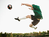 Caucasian soccer player in mid-air kicking soccer ball, Ladera Ranch, California, USA