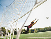 Mixed race goalkeeper in mid-air protecting goal, Ladera Ranch, California, USA
