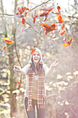 Mixed race woman in cap playing in autumn leaves, Seattle, WA, USA