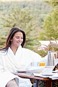 Woman enjoying breakfast on outdoor patio, Stowe, Vermont, USA