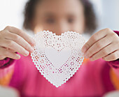 African American girl holding heart-shaped doily, Jersey City, New Jersey, USA