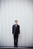 Serious groom standing near wall, San Francisco, California, USA