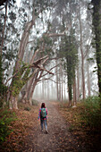 Korean woman in backpack walking in forest path, Bolinas, CA, USA