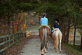 Caucasian girl and trainer riding horses, Manakin, VA, Goochland