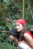 Hispanic man giving girlfriend piggyback ride in forest, El Retiro, Antioquia, Colombia