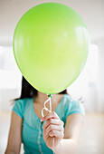 Korean woman holding balloon in front of her face, Jersey City, New Jersey, USA