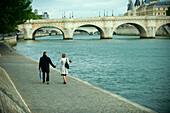 Caucasian couple holding hands and walking near river, Paris, Paris, France