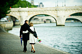 Caucasian couple hugging and walking near city river, Paris, Paris, France