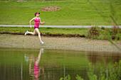 Mixed race woman running near pond, Bainbridge Island, WA, United States