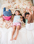 Girls playing on bed together, Jersey City, New Jersey, USA