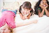Smiling girls laying on bed together, Jersey City, New Jersey, USA
