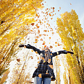 Caucasian woman playing with autumn leaves, Provo, Utah, USA