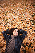 Caucasian woman laying in autumn leaves, Provo, Utah, USA