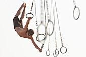 Mixed race man swinging on athletic rings, Santa Monica, California, United States