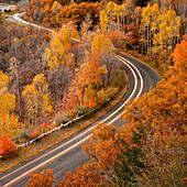 Long exposure of car driving on road through autumn leaves, Alpine, Utah, USA