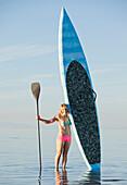 Caucasian woman standing in water with paddle board, Salt Lake City, Utah, USA