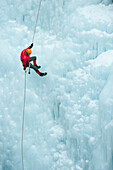 Caucasian man rappelling down ice wall, Ouray, Colorado, USA