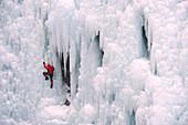Caucasian man climbing ice wall, Ouray, Colorado, USA