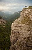 Caucasian man taking photographs from edge of cliff, Neuchatel, Neuchatel, Switzerland