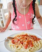 Mixed race girl eating spaghetti, Jersey City, New Jersey, USA