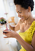 African American woman pouring red wine, Jersey City, New Jersey, USA