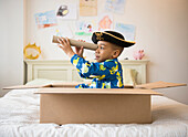African American boy playing in cardboard box, Jersey City, New Jersey, USA