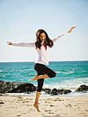 Mixed race woman jumping for joy on beach, Laguna Beach, California, USA