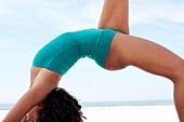 Mixed race woman practicing yoga on beach, Long Beach, NY, USA