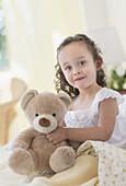 Mixed race girl holding teddy bear, Jersey City, NJ, USA