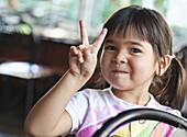 Asian girl making peace sign, Seattle, Washington, USA