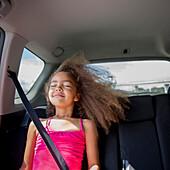 Mixed race girl enjoying wind in hair in back seat of car, Portland, OR, USA