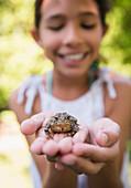 Mixed race girl holding frog outdoors, Huntington Station, New York, USA