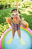 Mixed race girl wearing snorkeling gear in wading pool, Huntington Station, New York, USA