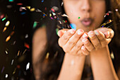 Close up of Asian woman blowing confetti from hands, Jersey City, New Jersey, USA
