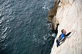 Mann beim Deep Water Soloing, Pula, Istrien, Kroatien
