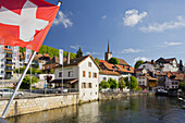 Swiss flag in the center of Vallorbe, Orbe river, Waadt, Switzerland