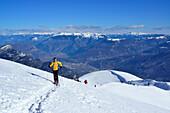 Female back-country skier ascending to Monte Baldo, alpine valley Etschtal in background, Monte Baldo, Garda Mountains, Trentino, Italy