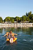 Woman paddling on an air mattress near a hotel beach, Vourvourou, Sithonia, Chalkidiki, Greece