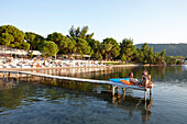 Couple on a pier at a hotel beach, Vourvourou, Sithonia, Chalkidiki, Greece