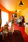 Woman touching a tiger figure in a hotel room, Saint-Saturnin-les-Apt, Provence, France