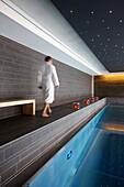 Guest walking along a hotel indoor pool, Adelboden, Canton of Bern, Switzerland