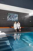 Couple sitting beside a hotel indoor pool, Adelboden, Canton of Bern, Switzerland