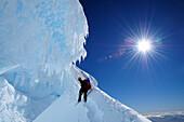 Mountaineer in a bergschrund of the north face of Monte Sarmiento, Cordillera Darwin, Tierra del Fuego, Chile