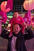 Happy man with young girl on his shoulders, Tsim Sha Tsui, Kowloon, Hong Kong